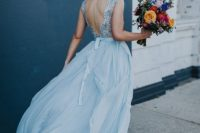 a beautiful ice blue winter wedding dress with a fully embellished bodice, a cut out back and a flowy and light skirt is adorable