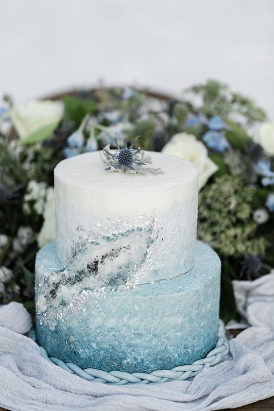 a beautiful ombre ice blue winter wedding cake with crystals and a thistle on top the cake is lovely
