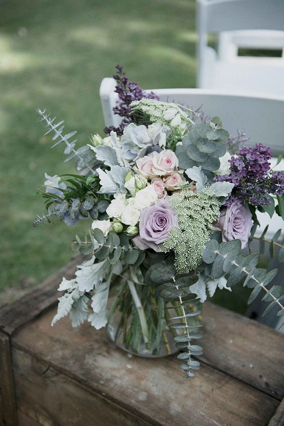 a beautiful wedding centerpiece of purple, lavender, blush and white blooms and with lots of greenery from mint to darker greens