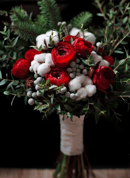 a beautiful winter wedding bouquet of red roses, cotton, berries and greenery and fir branches is a fit for a Christmas wedding