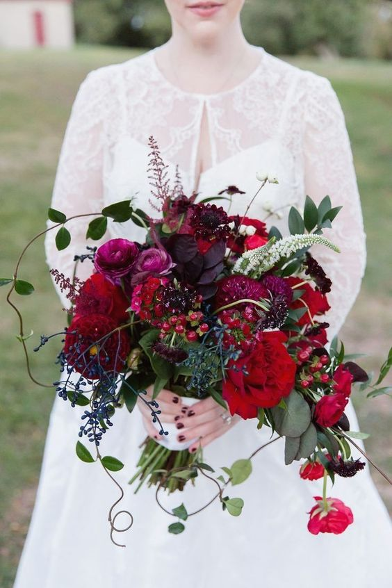 a berry-hued Christmas wedding bouquet of red, fuchsia, purple blooms, berries and greenery features a cool shape