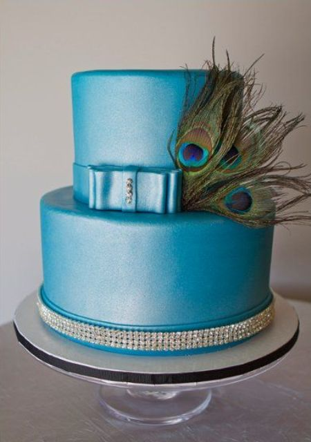 a blue wedding cake decorated with rhinestones and peacock feathers is a very creative and bold idea