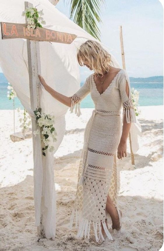 a boho beach crochet wedding dress with a slit, short sleeves, a V-neckline, fringe on the skirt and sleeves for a lovely look