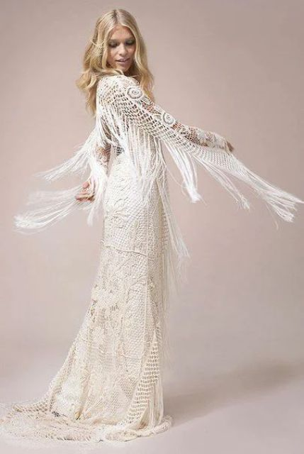 a boho crochet mermaid wedding dress with long fringe on the back and sleeves, a small train feels very wild and free-spirited