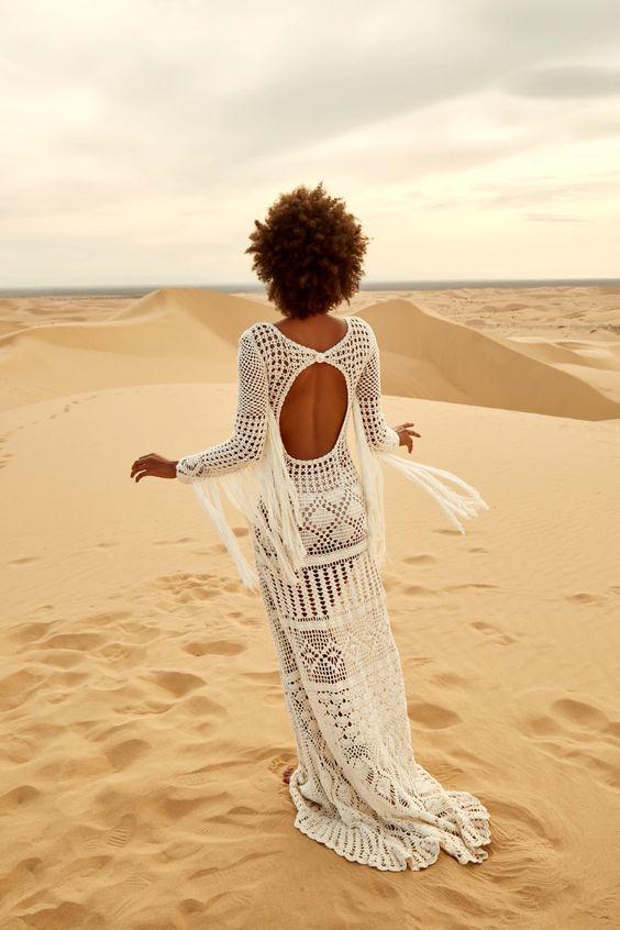 a boho mermaid crochet wedding dress with long fringe on the sleeves, a cutout back is a gorgeous idea for a desert wedding