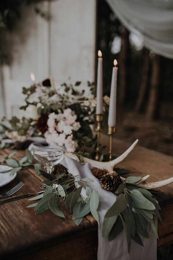 a boho woodland wedding centerpiece of greenery, neutral blooms, pinecones, tall and thin candles is a lovely idea