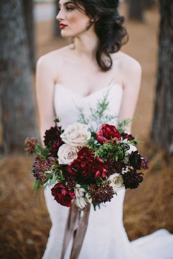 a bold Christmas wedding bouquet of blush, burgundy and deep purple blooms, berries and greenery
