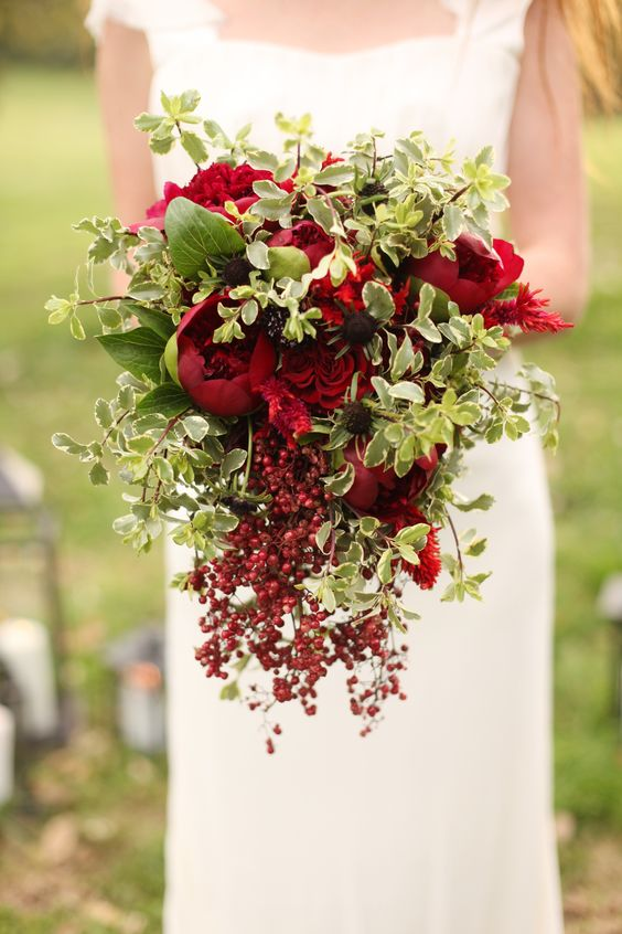 a bold Christmas wedding bouquet of red and burgundy blooms and greenery plus cascading berries for a catchy touch