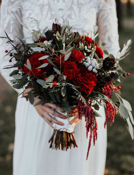 a bold Christmas wedding bouquet of red and deep purple blooms, greenery and berries is very chic