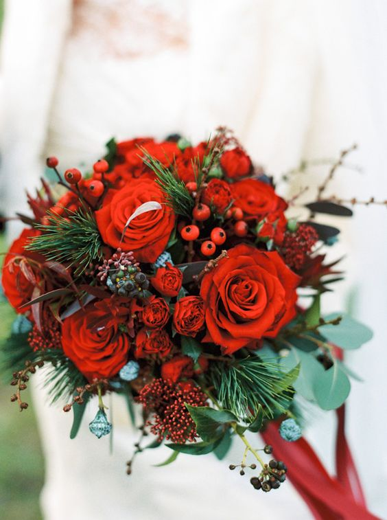 a bold Christmas wedding bouquet of red blooms, berries, greenery and fir branches is bright