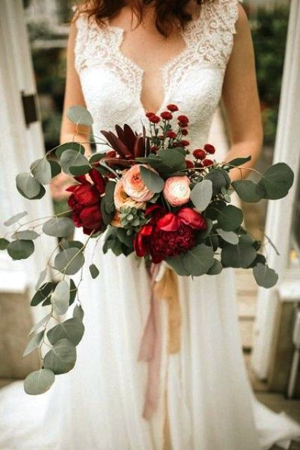 a bold Christmas wedding bouquet of red, blush and peachy blooms and lots of cascading greenery