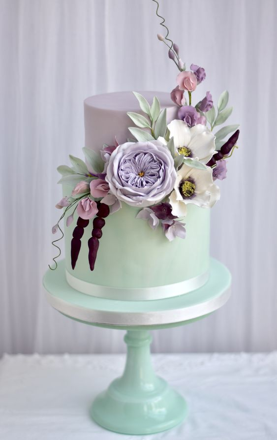 a bold mint and lavender wedding cake decorated with white, blush, purple and lavender sugar blooms and greenery