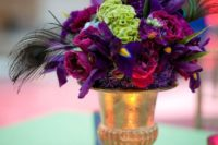 a bold wedding centerpiece with a gold urn, deep purple blooms and green ones plus peacock feathers