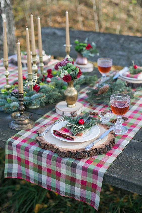 a bright Christmas tablescape with a plaid runner, evergreens, pinecones, gold candles and bright red and green blooms
