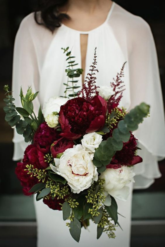 a bright Christmas wedding bouquet of burgundy and blush peonies and greenery that creates a bold shape