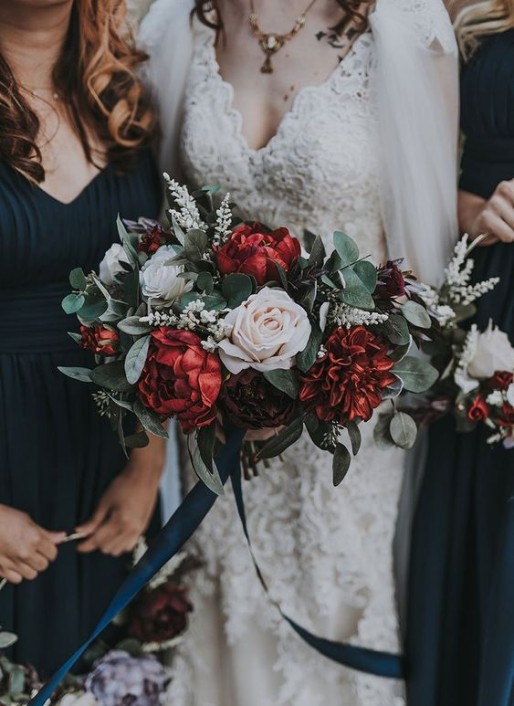 a bright Christmas wedding bouquet of burgundy and white blooms, greenery and white blooming branches