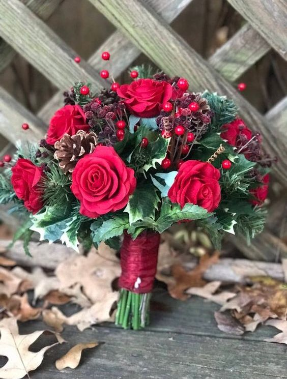 a bright Christmas wedding bouquet of red roses, berries and dried berries, pinecones and lots of greenery