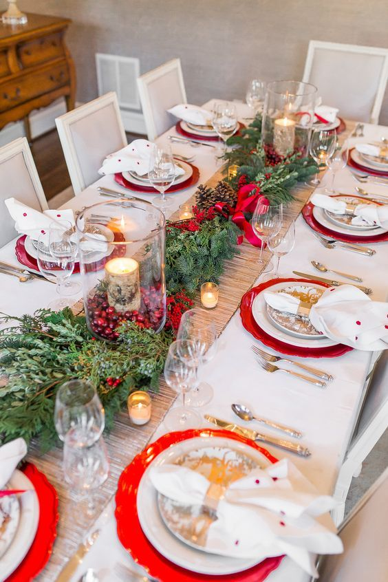 a bright Christmas wedding table with red chargers, an vergreen and pinecone runner, cranberries and birch bark candles, printed plates and polka dot napkins