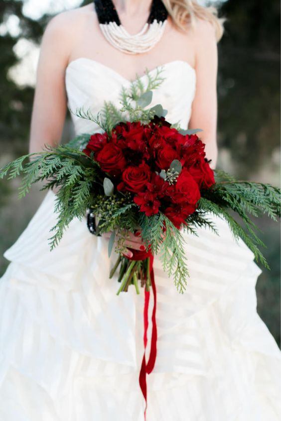 a bright and chic Christmas wedding bouquet of red roses and ferns plus red ribbons is gorgeous