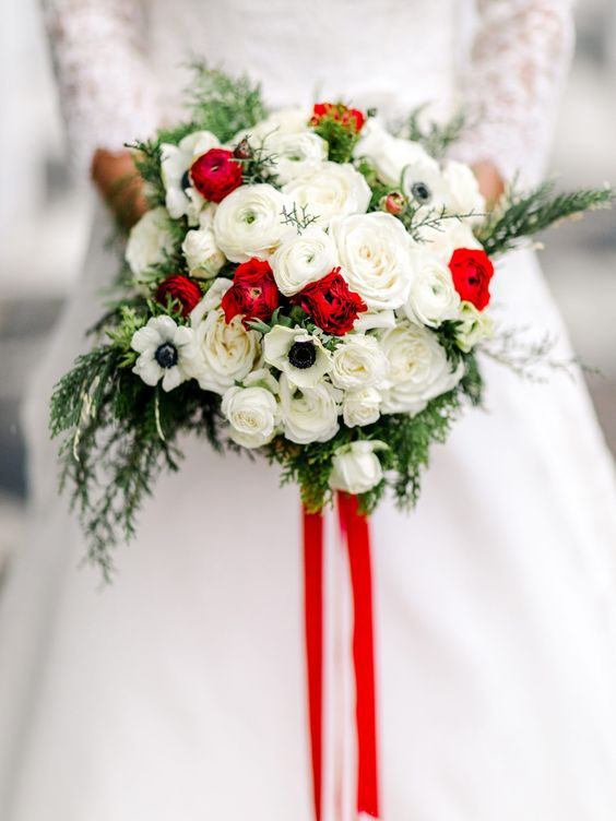 a bright traditional Christmas wedding bouquet of white and red blooms, greenery and red ribbons is a bold accessory