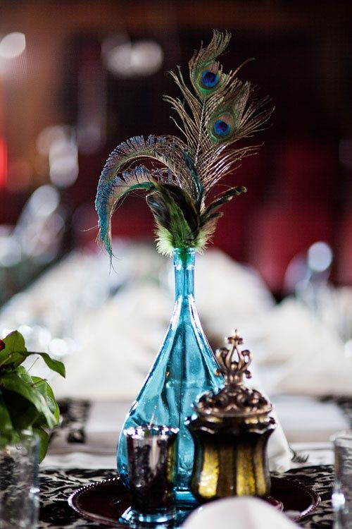 a bright wedding centerpiece of a blue bottle, feathers and peacock feathers for a Moroccan or boho wedding