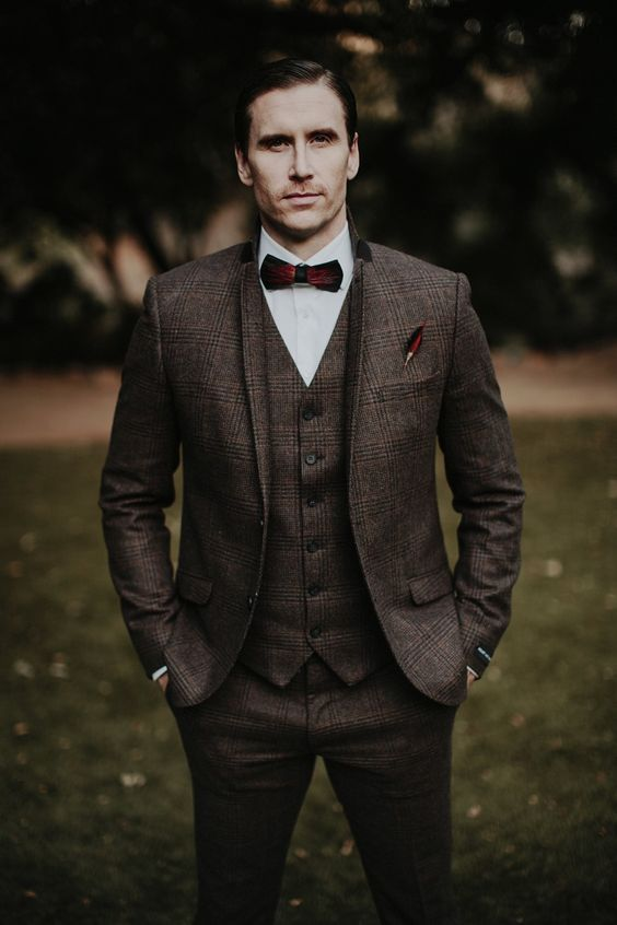 a brown plaid tweed three-piece suit, a white button down, a burgundy bow tie for an elegant winter look