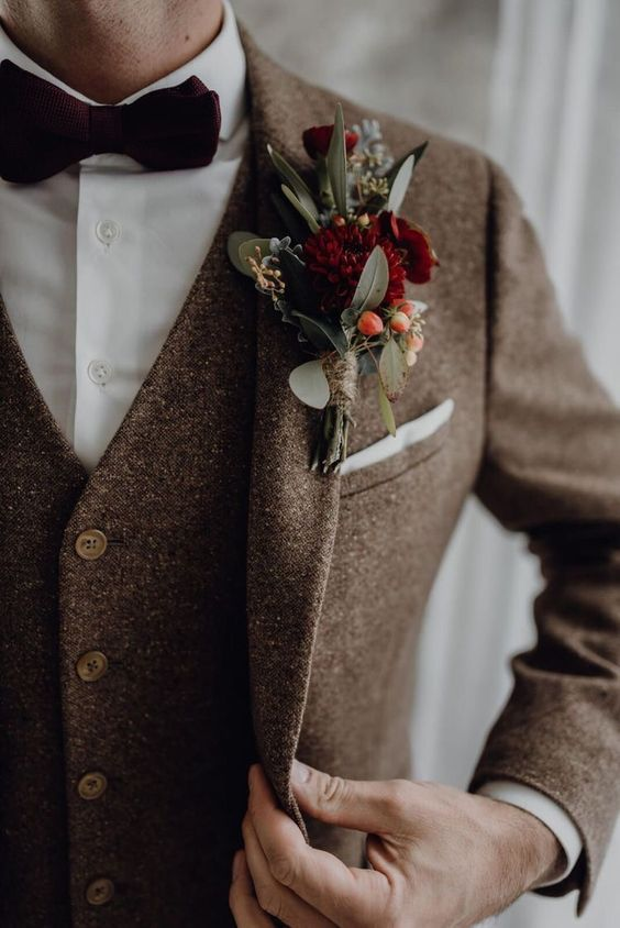 a brown tweed three-piece suit, a white button down, a burgundy velvet bow tie and a matching boutonniere