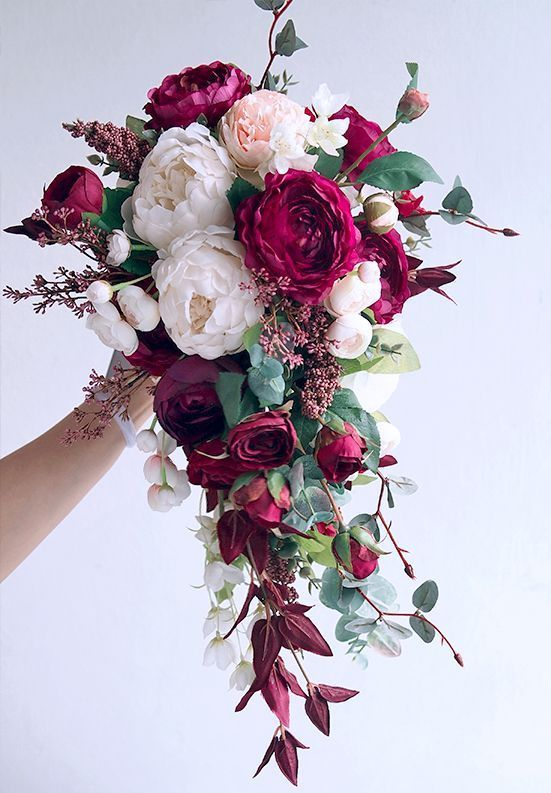 a cascading Christmas wedding bouquet of blush and burugundy blooms, greenery, bold leaves and herbs