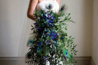 a cascading greenery wedding bouquet with purple orchids and peacock feathers will make a statement