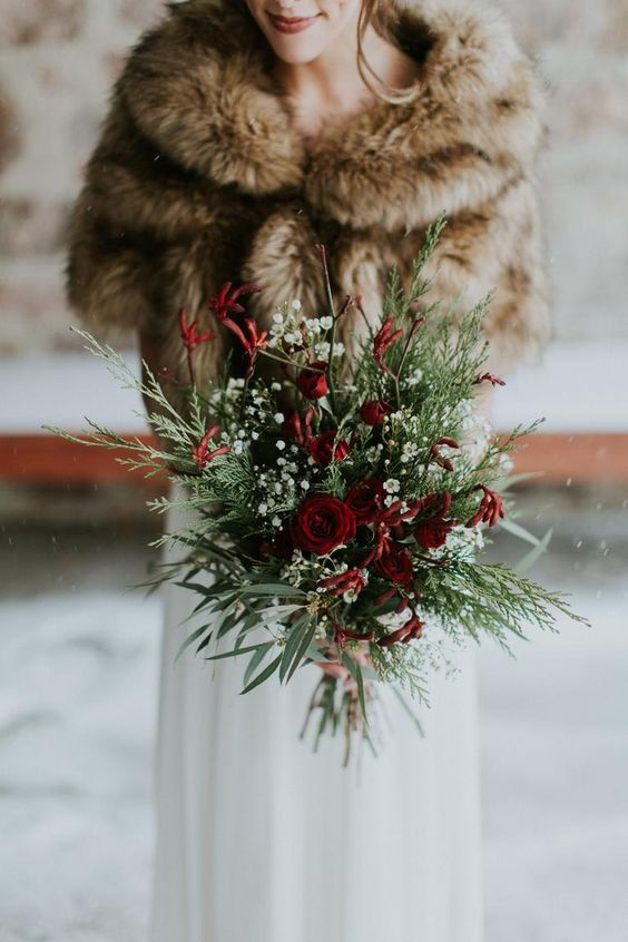 a catchy shaped Christmas wedding bouquet of burgundy blooms, baby's breath and greenery