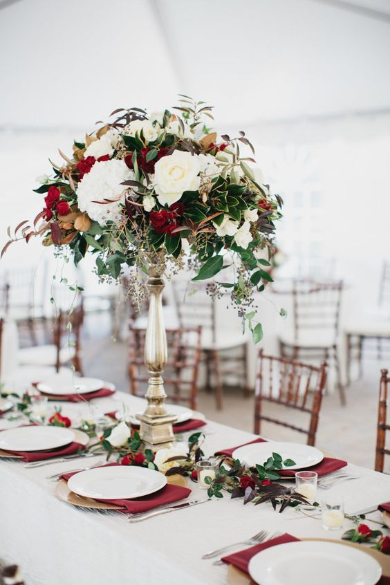 a chic Christmas tablescape with a greenery and red bloom runner and a matching tall centerpiece, burgundy napkins and gold chargers