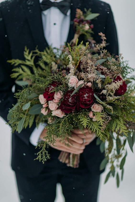 a chic Christmas wedding bouquet of greenery, eucalyptus, blush and burgundy blooms shows off much texture