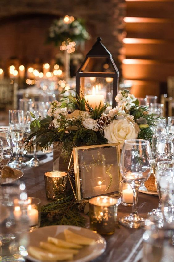 a chic Christmas wedding centerpiece of white blooms, fir branches, pinecones and a glass candle lantern is adorable