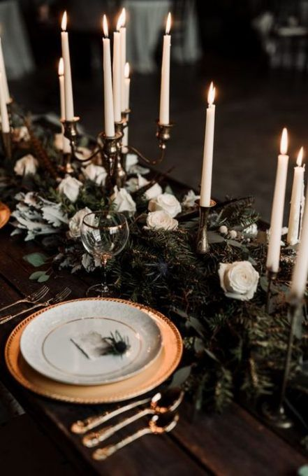 a chic and refined Christmas tablescape with an evergreen runner with white roses, tall and thin candles, gold chargers and white porcelain