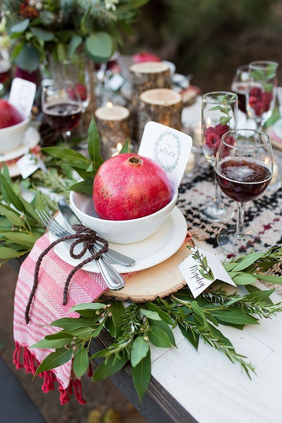 a chic rustic Christmas tablescape with a plaid runner and a striped napkin, greenery, pomegranates, tree stump candleholders and burgundy blooms