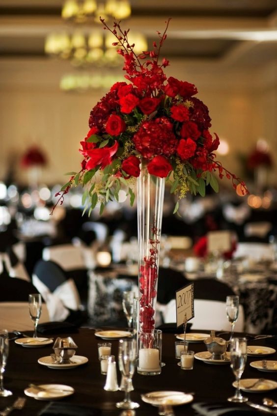 a colorful Christmas wedding centerpiece of a tall glass vase with petals and a candle and a bold floral and greenery arrangement