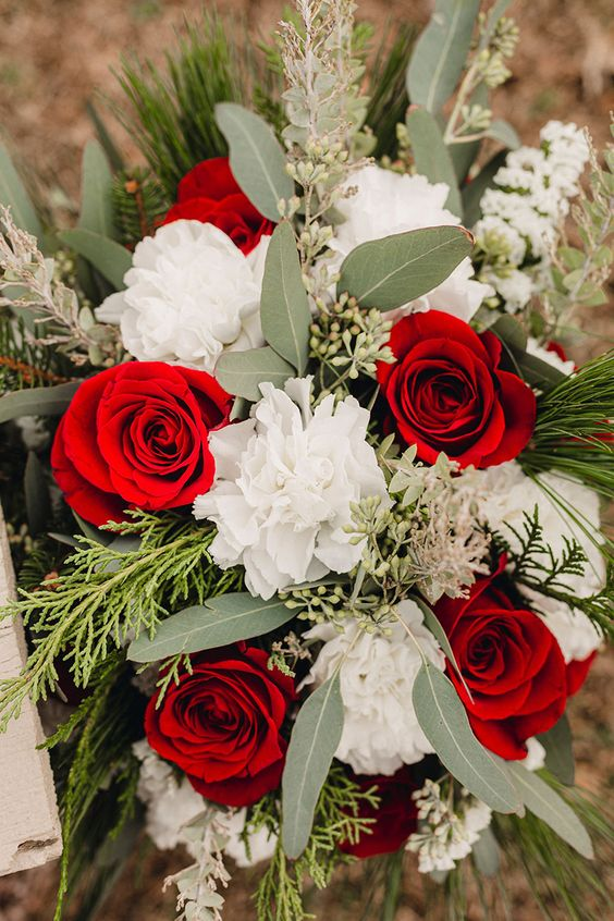 a contrasting Christmas wedding bouquet of red and white blooms, greenery and fir branches