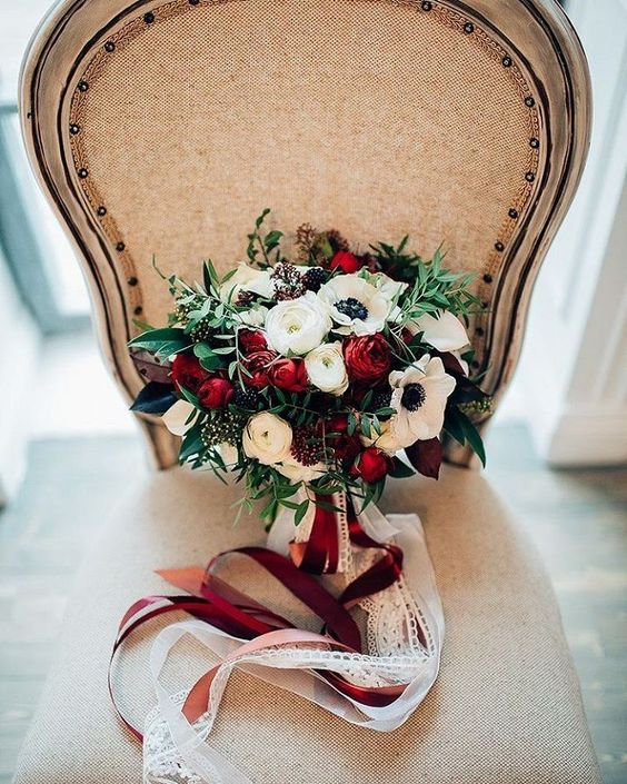a contrasting Christmas wedding bouquet of red and white flowers, greenery, burgundy and white ribbons