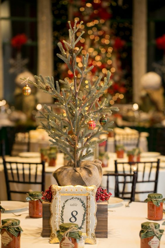 a cool Christmas wedding centerpiece of a mini tree with pinecones and lights, a berry wreath and a framed table number