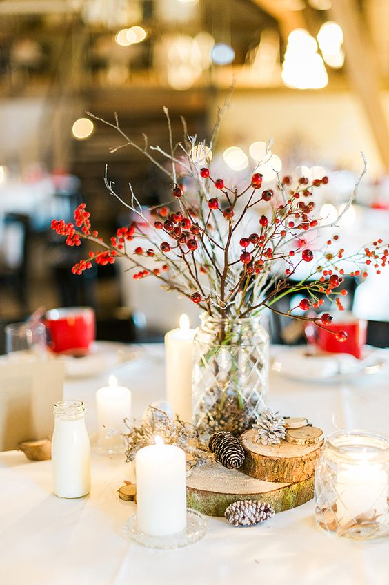 a cozy rustic Christmas wedding centerpiece of a vase with berried branches, wood slices, pinecones and candles around