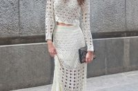 a creative crochet two piece wedding dress with a crop top with long sleeves and a maxi skirt, two tone shoes and an embellished clutch