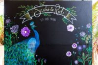 a creative wedding backdrop with a peacock and bright blooms, names and a date – all painted by an artist