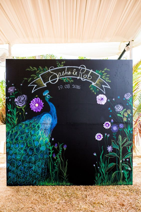 a creative wedding backdrop with a peacock and bright blooms, names and a date - all painted by an artist