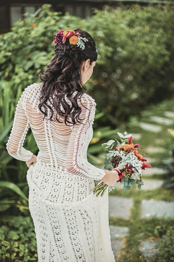 a crochet A-line wedding dress with an illusion back and long sleeves, a bold floral hairpiece and a bouquet for a boho summer or fall bride