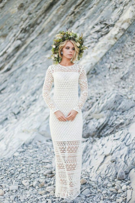 a crochet A-line wedding dress with an illusion neckline and long sleeves, a greenery and neutral floral crown for a cool boho bridal look
