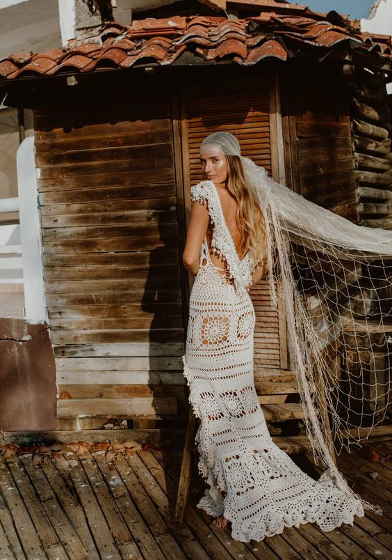 a crochet fitting wedding dress with a slit, an open back, a veil and a short train for a lovely boho bridal look