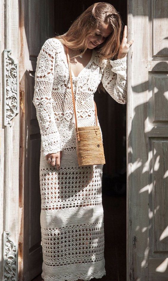 a crochet fitting wedding dress with various patterns, with a V-neckline and long sleeves plus a woven bag for a boho summer bride