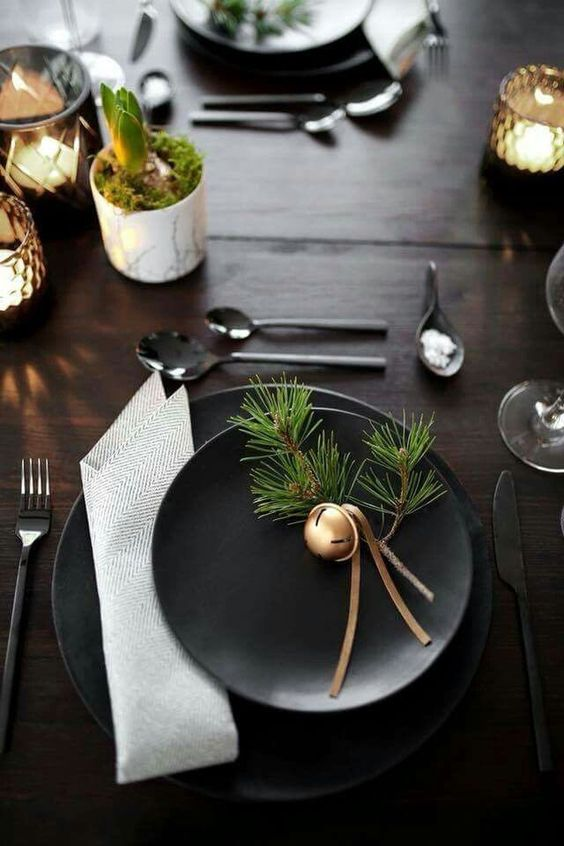 a dark Christmas tablescape with black plates, evergreens, bells, printed napkins, candles and bulbs