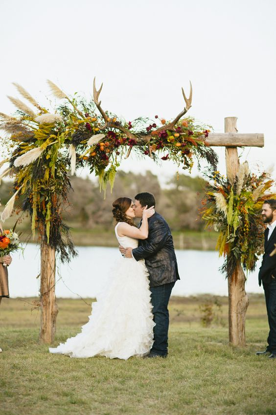 a fall wedding arch decorated with greenery, pampas grass, berries, bright blooms and antlers is a beautiful decoration