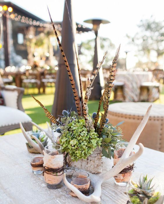 a fall wedding centerpiece of green hydrangeas, thistles, feathers, antlers and candles in glasses wrapped with birch bark